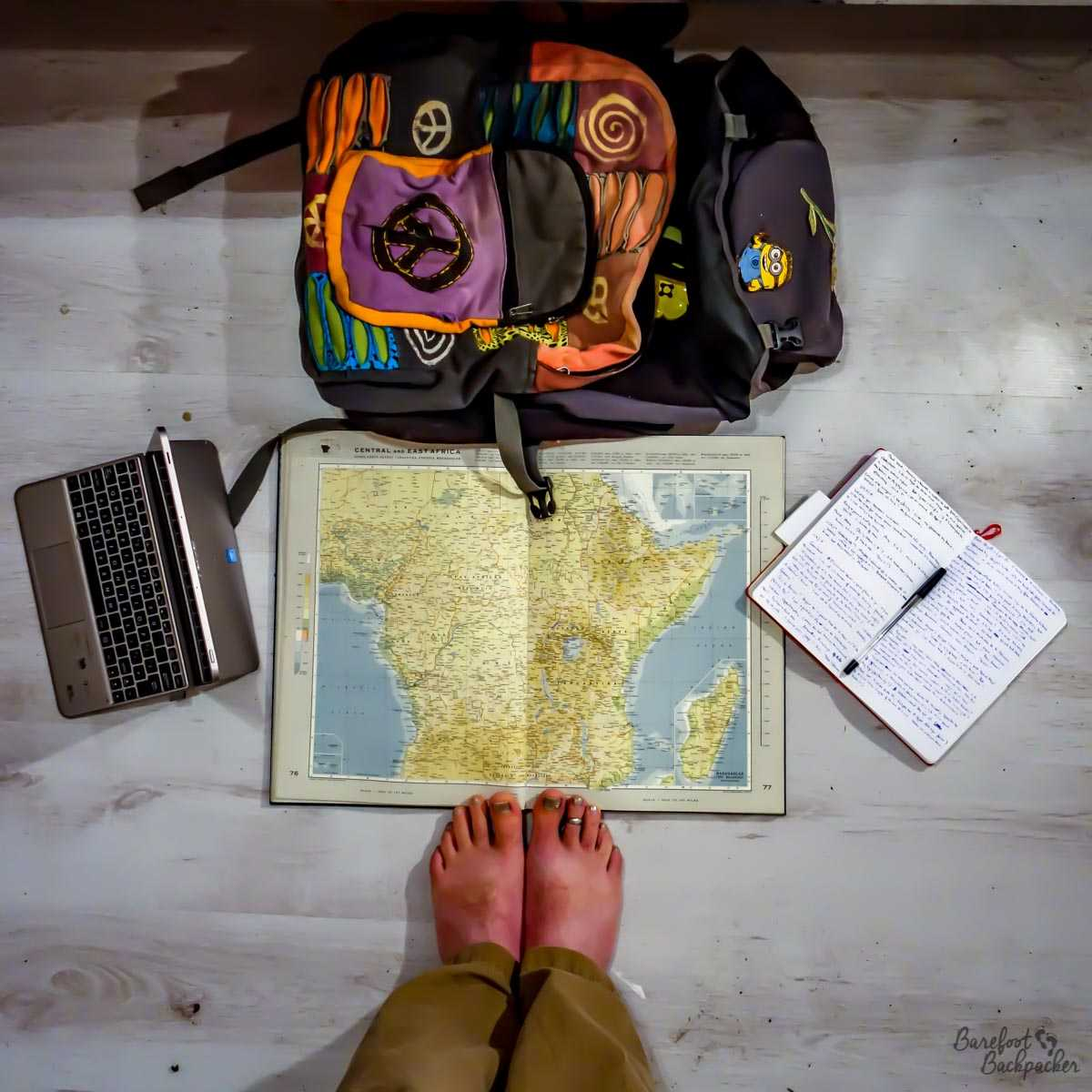 Travel blogger, with feet, map, backpack, notepad, and tablet. Everything the travel blogger needs to survive!