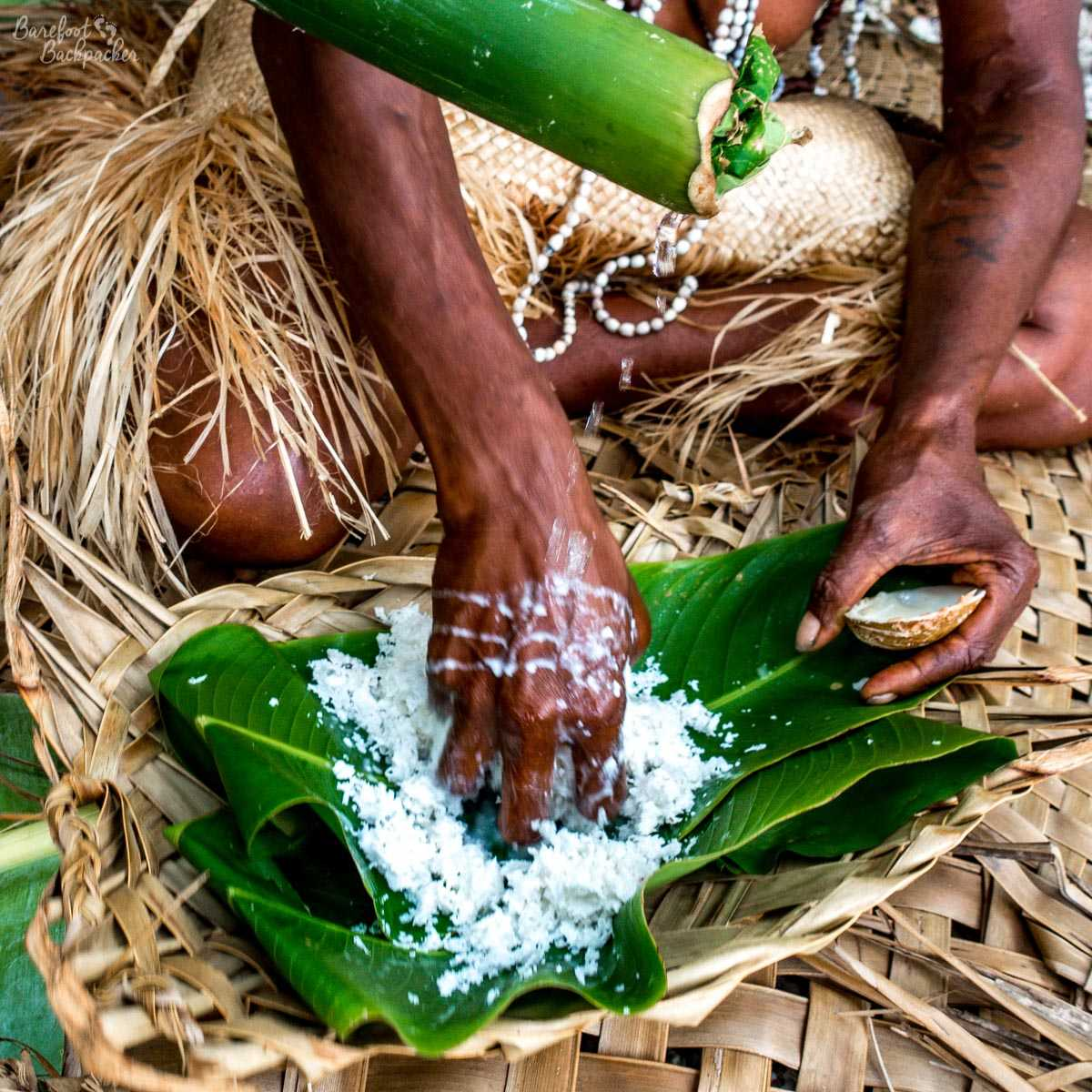 A tribeswoman making coconut milk.