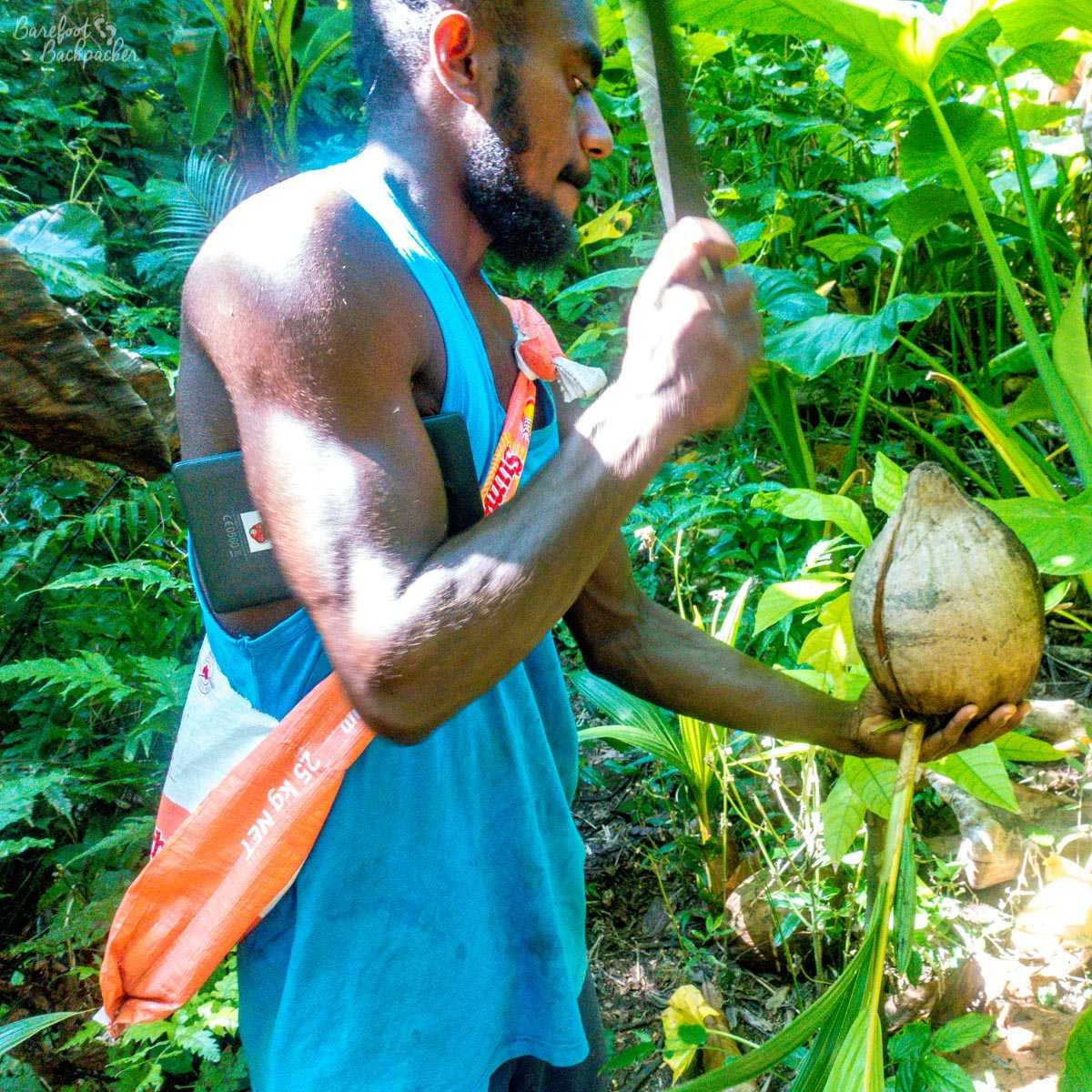 My guide cutting a coconut with a machete.