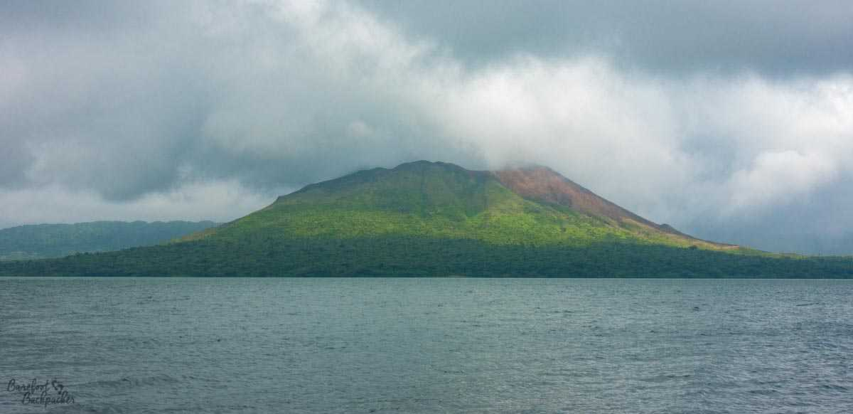 Mount Garet, Gaua, as seen across Lake Letas, cloudy.
