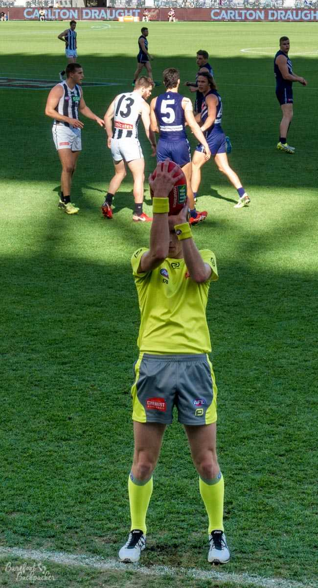 Umpire throwing in the ball during an AFL game at Optus Stadium, Perth