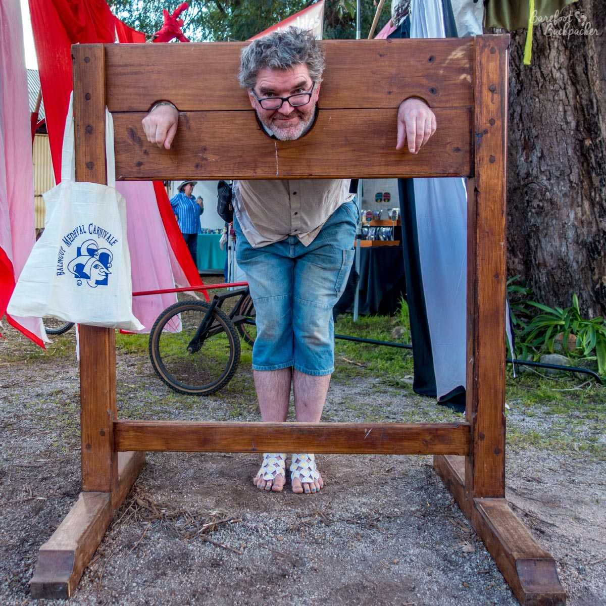 The Barefoot Backpacker locked in a pillory, Mediaeval Carnivale, Balingup