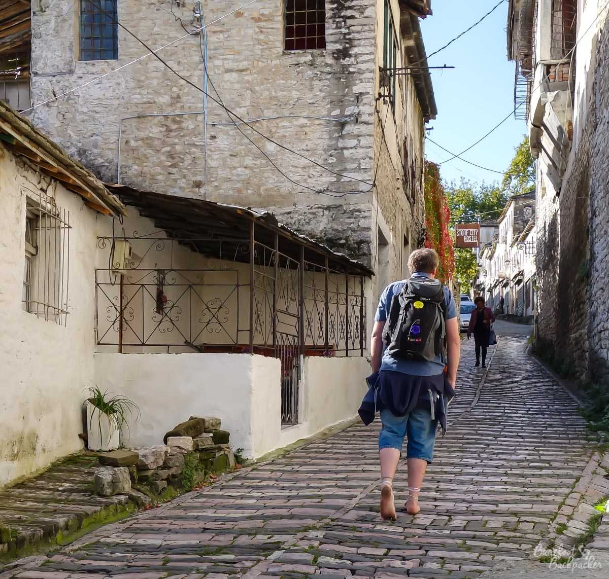 Walking barefoot with a backpack through the cobbled streets of Gjirokaster, in Albania