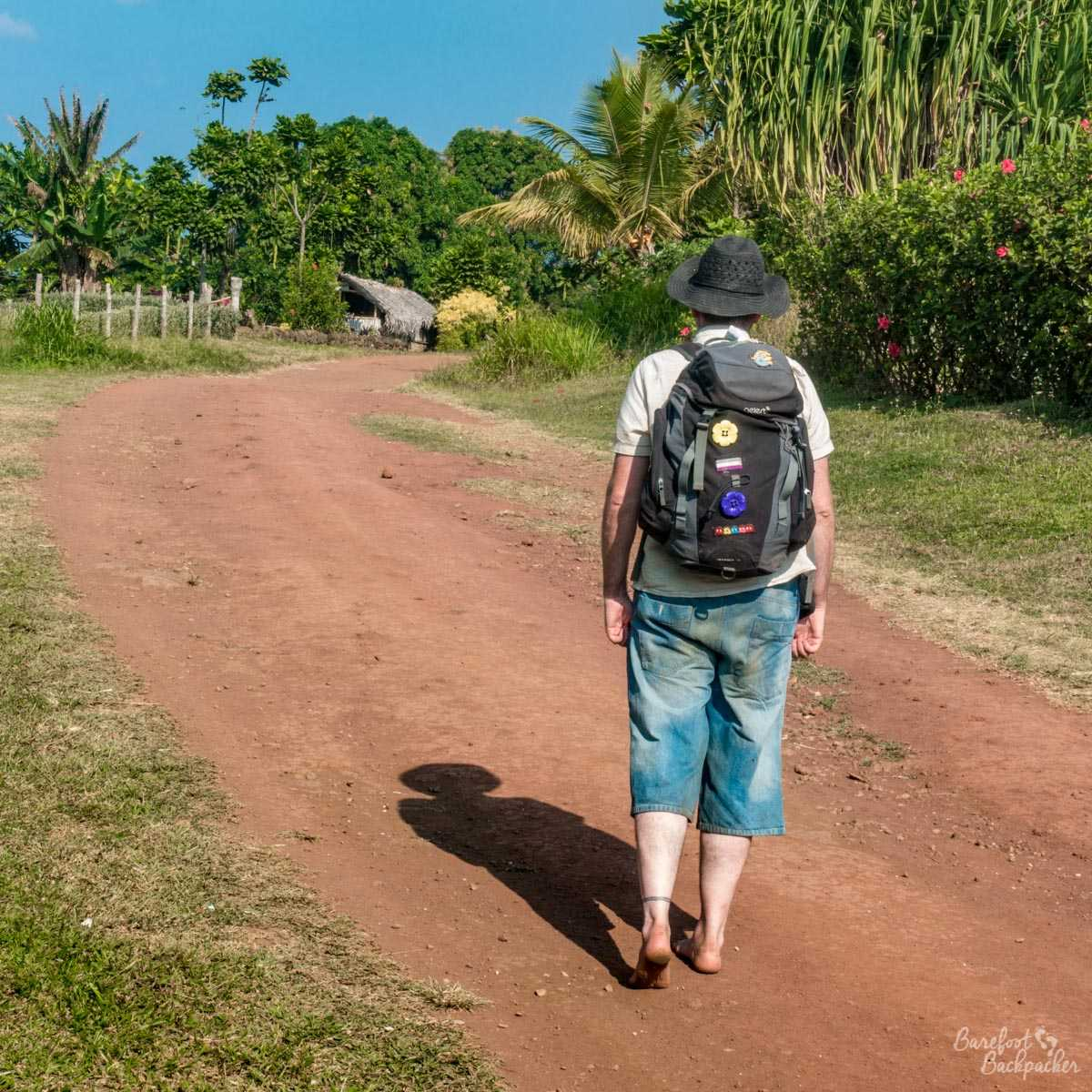 Man (me, obviously) walking down a stony, dusty, orange road on the island of Gaua in Vanuatu. There's trees on the right, bushes on the left, cottages in the distance, and blue sky. The man is barefoot, wearing three-quarter length blue jeans, and is carrying a backpack which fits in hand luggage on an aeroplane.