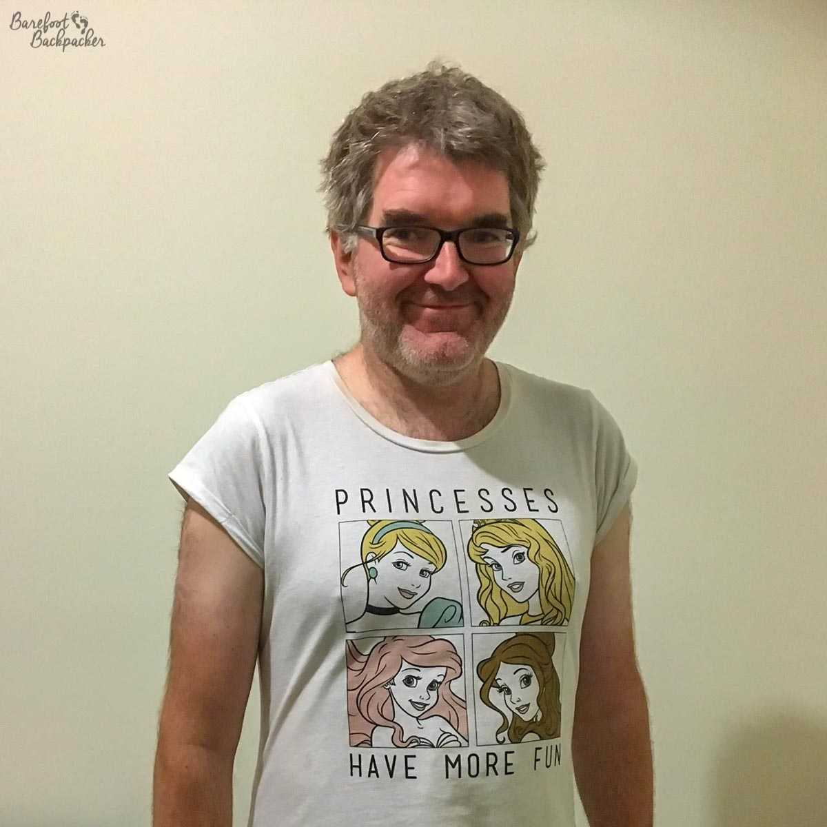 Picture of me, taken by my friend Lisa in Australia, where I am wearing one of her T-shirts proclaiming 'Princesses Have More Fun', with four cartoonish images of princesses' heads on it. The most disturbing thing about it is that the t-shirt fits me. Also, moobs.