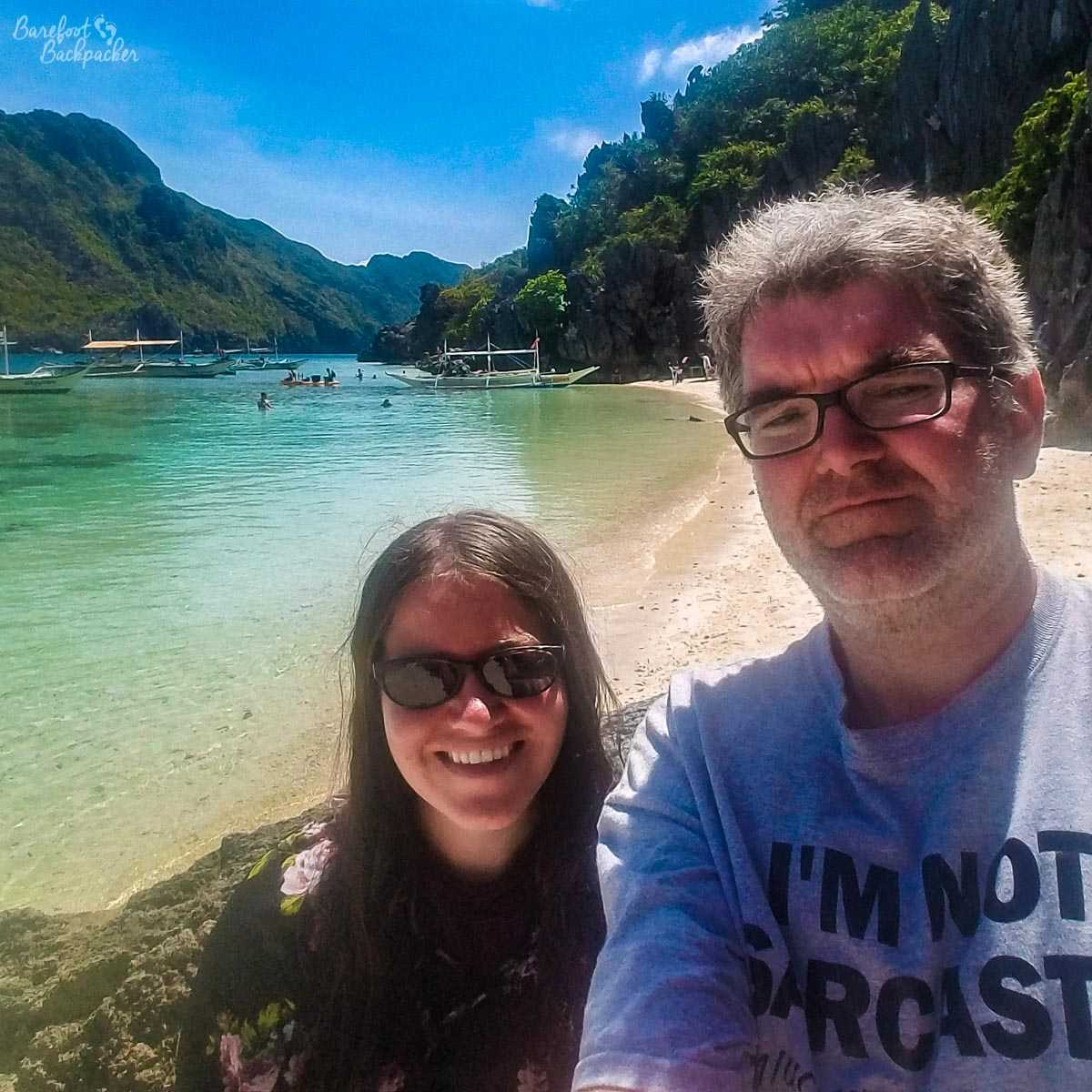 The Barefoot Backpacker not travelling solo for once. Rather he is with Laura (from Tumbleweed Chronicles), standing on the beach at Helicopter Island, in Philippines