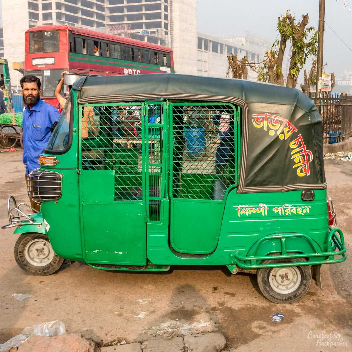 A CNG (gas-powered auto-rickshaw) in the parking bay at the Airport railway station in Dhaka, Bangladesh. It's basically a metal cage on wheels. The standard method of travel across the city. Scary af!