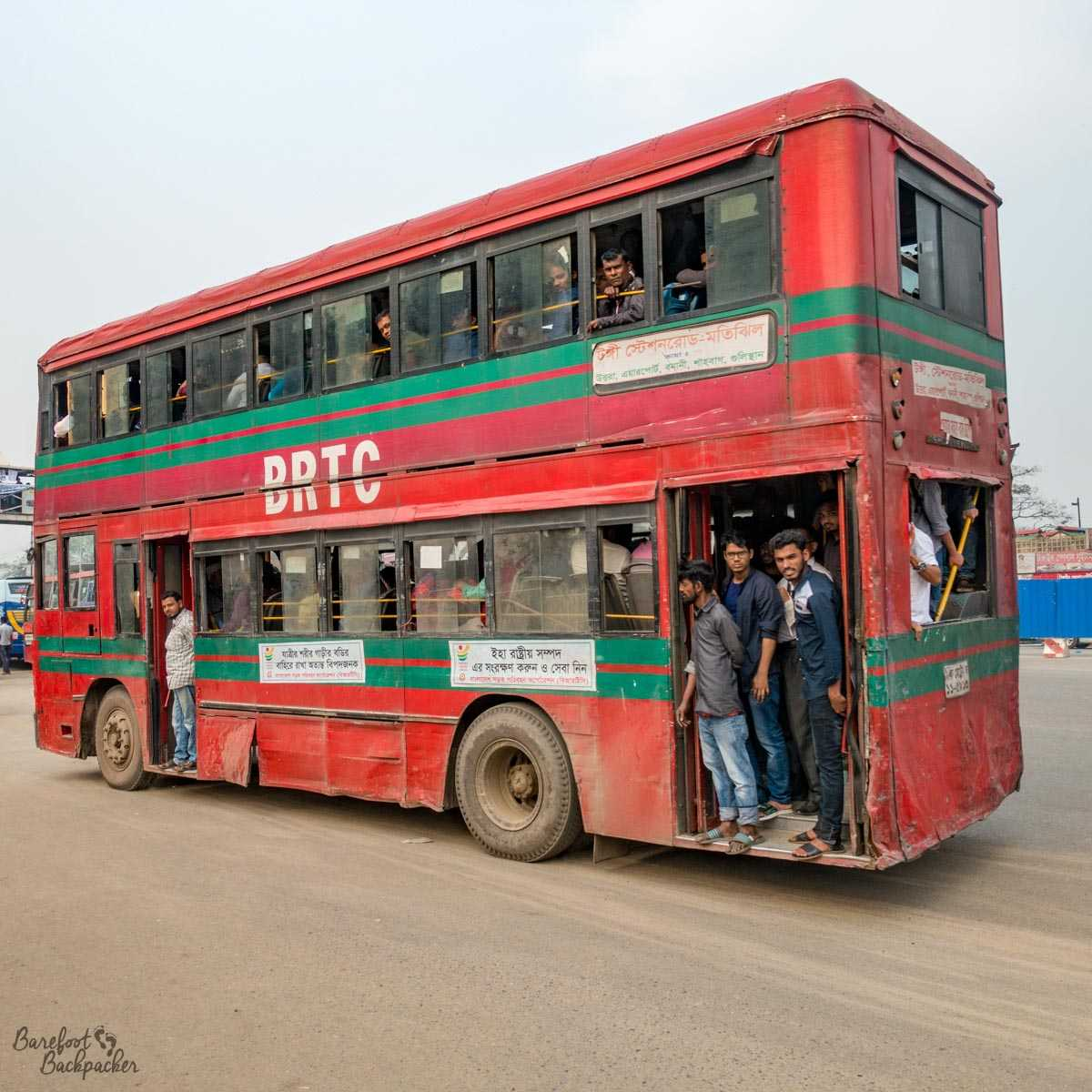 A typical bus in Dhaka – it's a red double-decker, it looks pretty old, and it's completely full to the extent that there are people just standing at the open door at the rear. They are not waiting to get off.