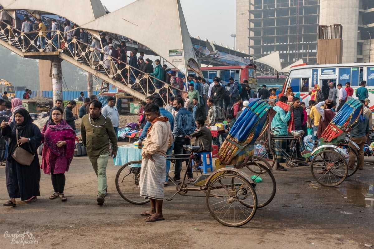 Street scene near Dhaka Airport Railway Station, with crowded footbridge, and a mass of rickshaws and stalls.