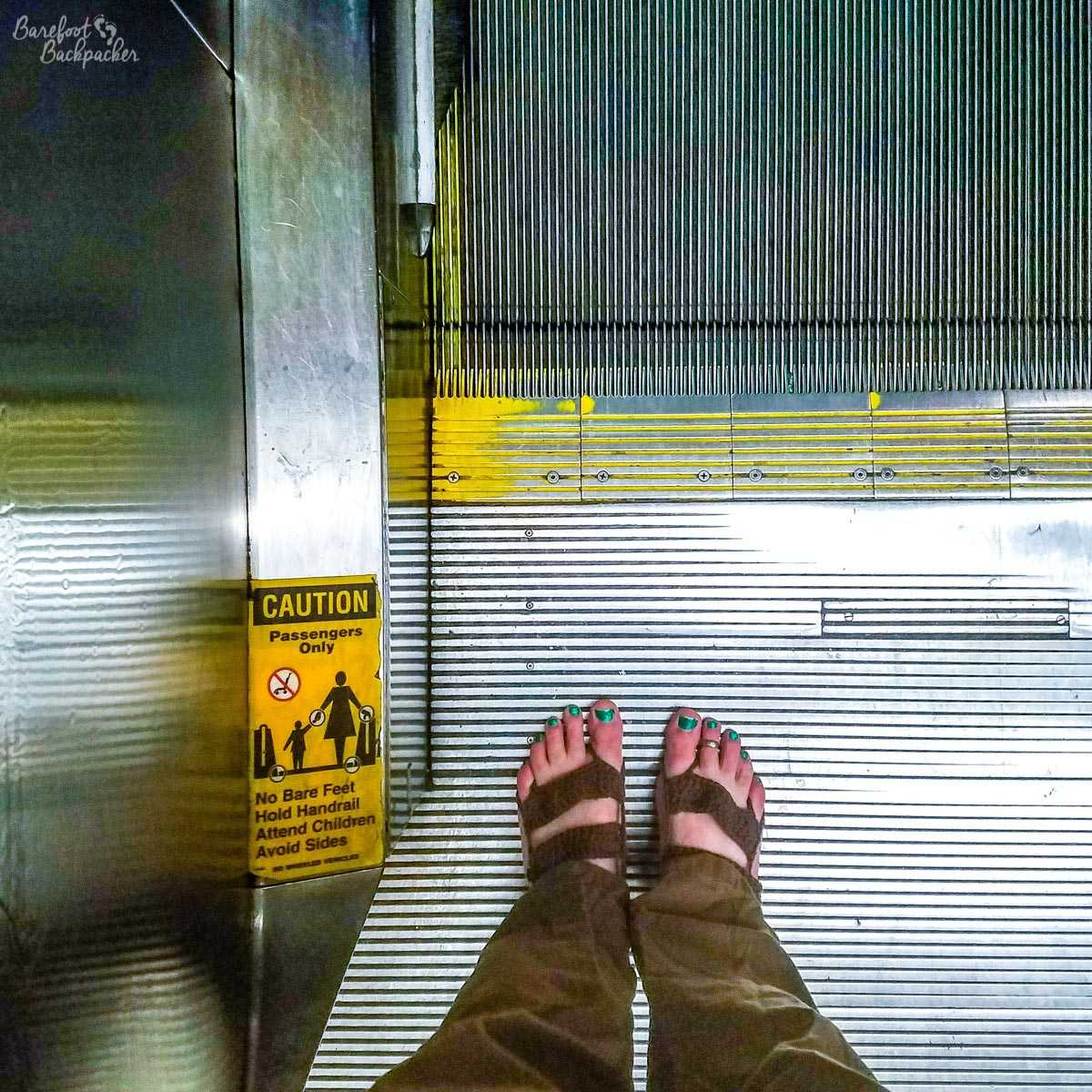 Barefoot on an escalator in an airport, next to a sign that says 'no bare feet'. I am such a rebel.