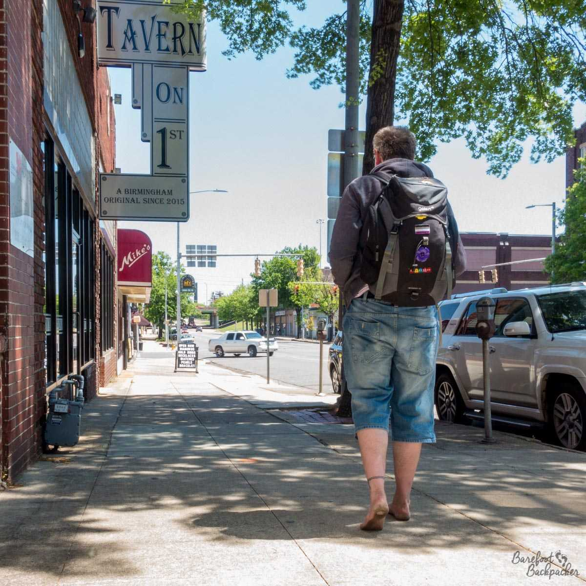 Walking barefoot with a backpack down a street in Birmingham, Alabama