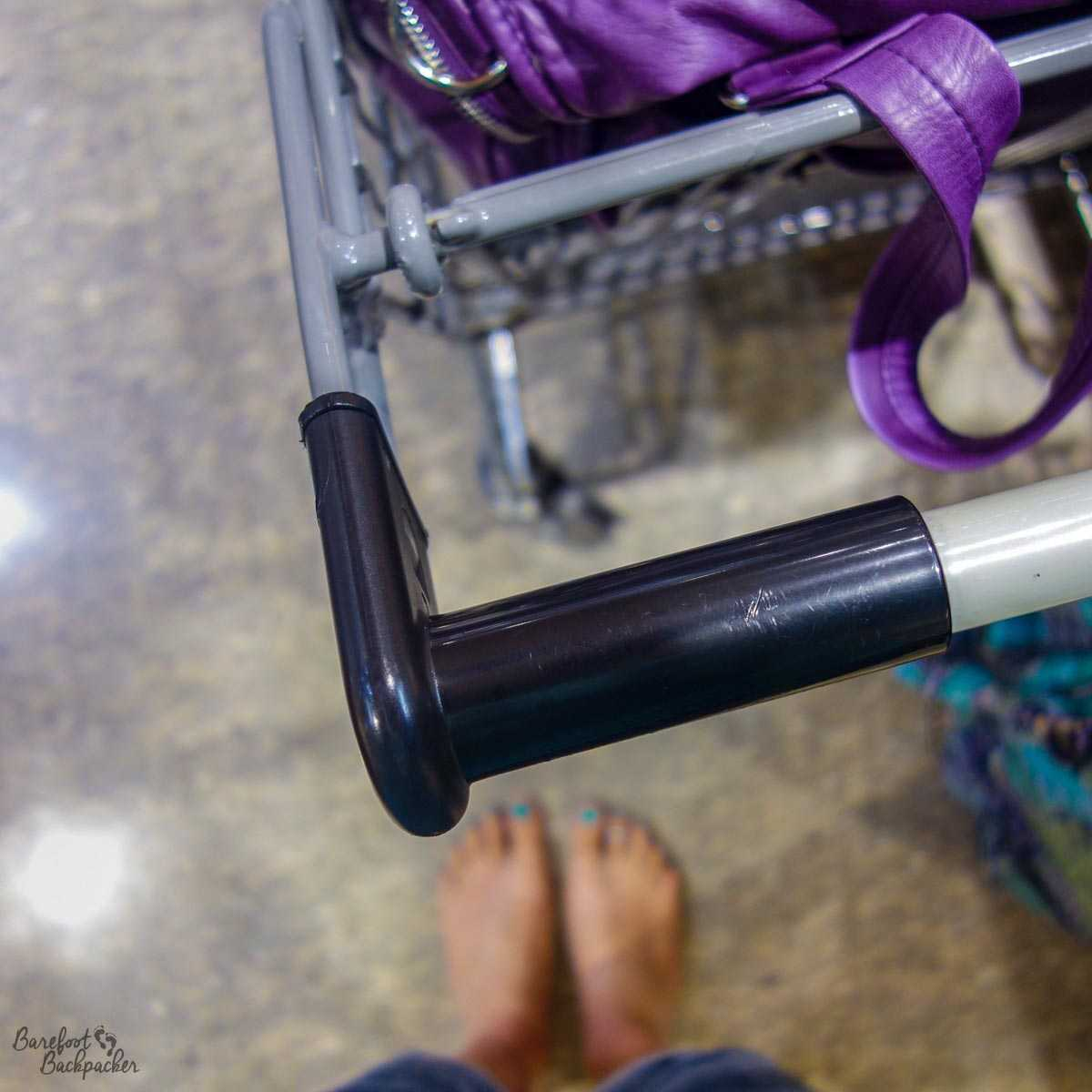 Barefoot in a supermarket in Nambour, Australia; feet in the background out of focus; a shopping trolley in the foreground, a purple bag in the trolley.