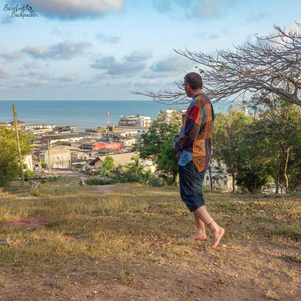 Standing barefoot, overlooking the city of Cape Coast, in Ghana