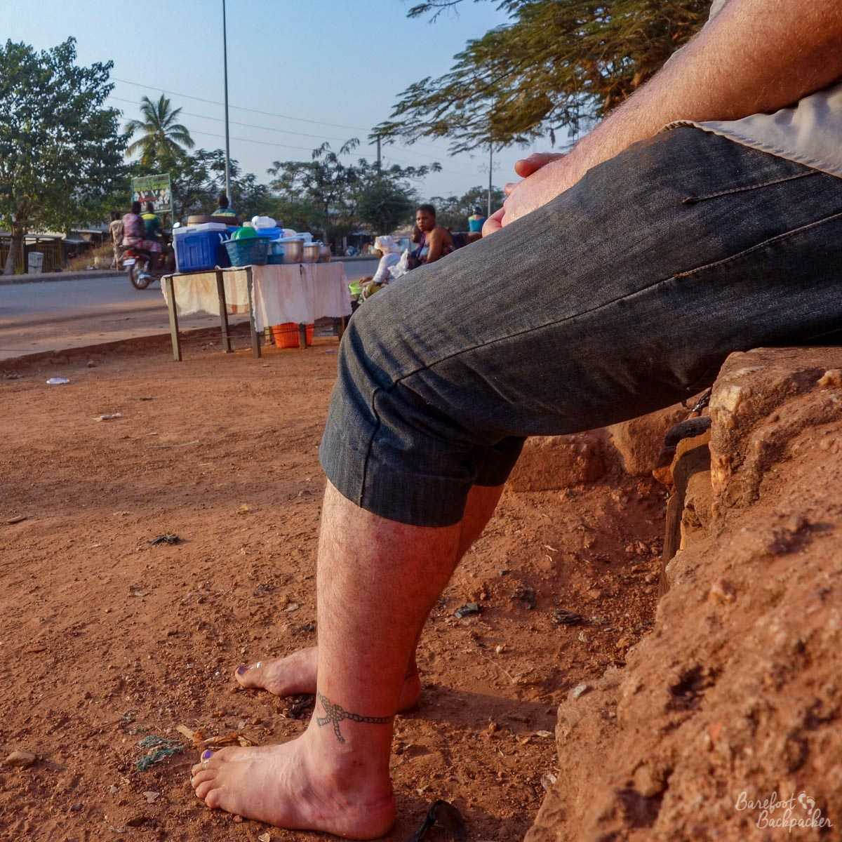 Sitting barefoot by a roadside in Natitingou, Benin, while a woman watches on