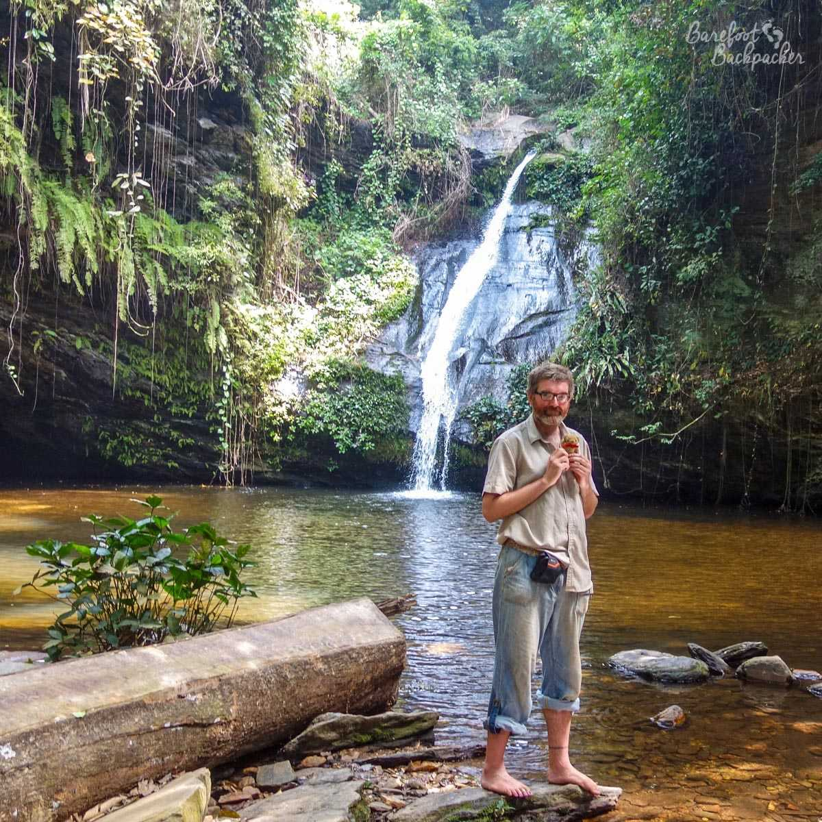 The Barefoot Backpacker standing in front of the waterfalls at Wome, Western Togo