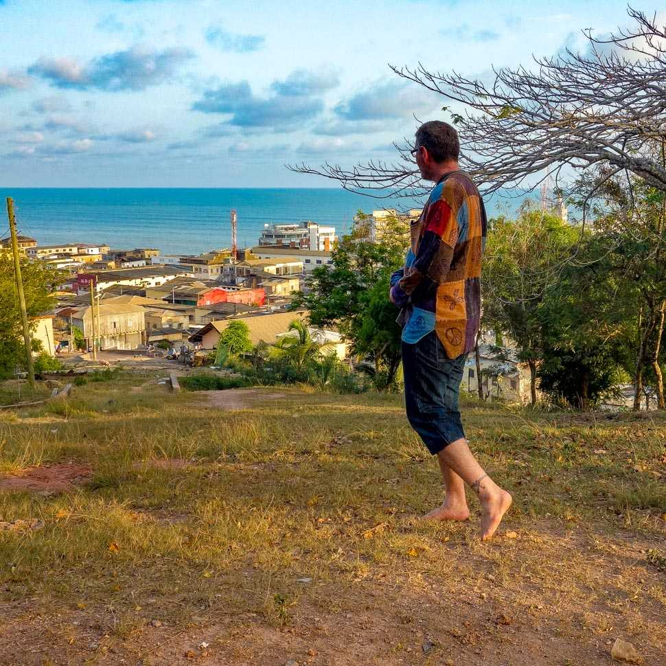 The Barefoot Backpacker standing on the hill at Fort William overlooking Cape Coast, Ghana