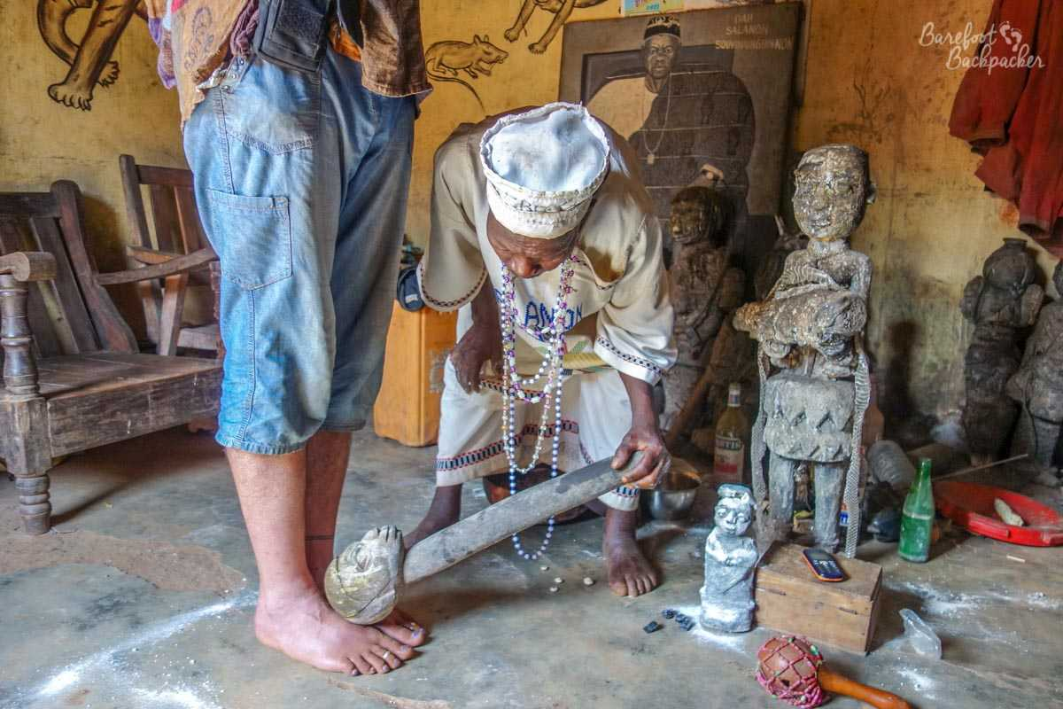 Partway through a Vodun ceremony – the Barefoot Backpacker is having his feet tapped with a stone totem by the Vodun priest.