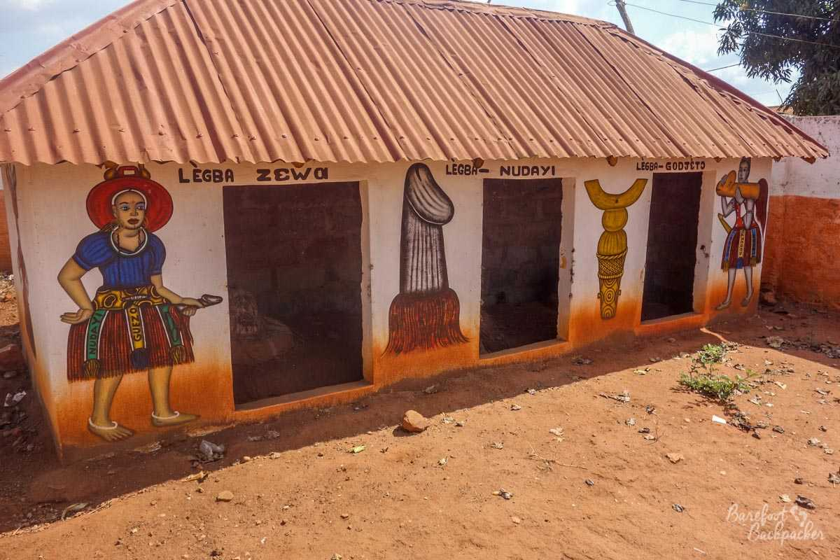 A temple in Abomey dedicated to Legba; the outside of the temple has various painted motifs of the spirit god in question. All of them holding his manhood proudly.