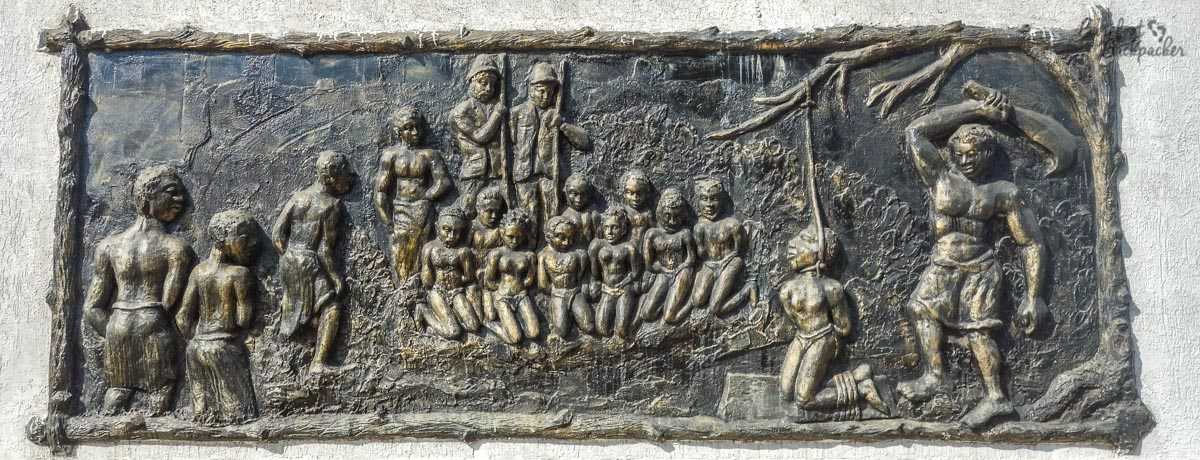 One of the many friezes adorning the wall of the Da Silva museum in Porto Novo. It's one of the milder ones – it shows a group of kneeling captives, with colonial westerners standing behind with guns. On the right is someone kneeling naked on the ground, hands tied behind them, feet tied together, a noose around their neck, being whipped.