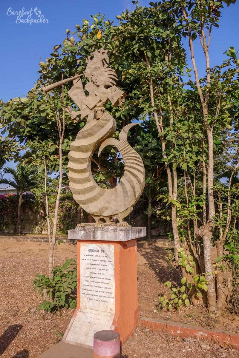 The 'tree of forgetfulness' along the 'Route Des Esclaves' in Ouidah. I'm not quite sure what it is – a dragon or snake smoking a pipe is my best guess – but it stands at the spot where future slaves were forced to walk around one of the trees in the background, to confuse and to ram home just how subservient they were.