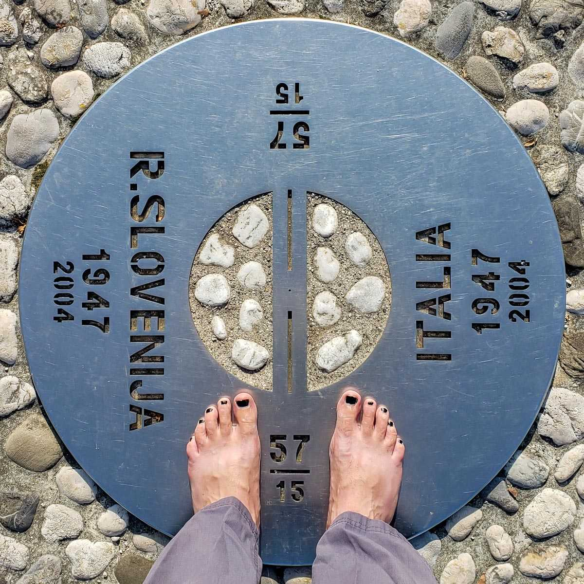Standing barefoot on the metal circular plaque that marks the old Iron Curtain boundary between Italy and Slovenia, in the towns of Gorizia/Nova Gorica.