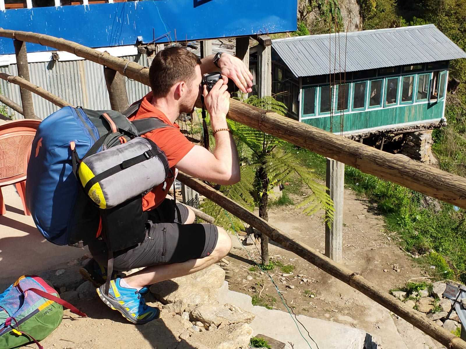 Man (Alexei, from Travelexx) on the edge of a cliff, squatting down behind a wooden fence-like structure made of poles. He is taking a photograph with a camera of whatever is on the other side of the fence/down from the cliff. He has a backpack on, he is also carrying a sleeping bag shaped item on his back, and there's another small pack by his feet.
