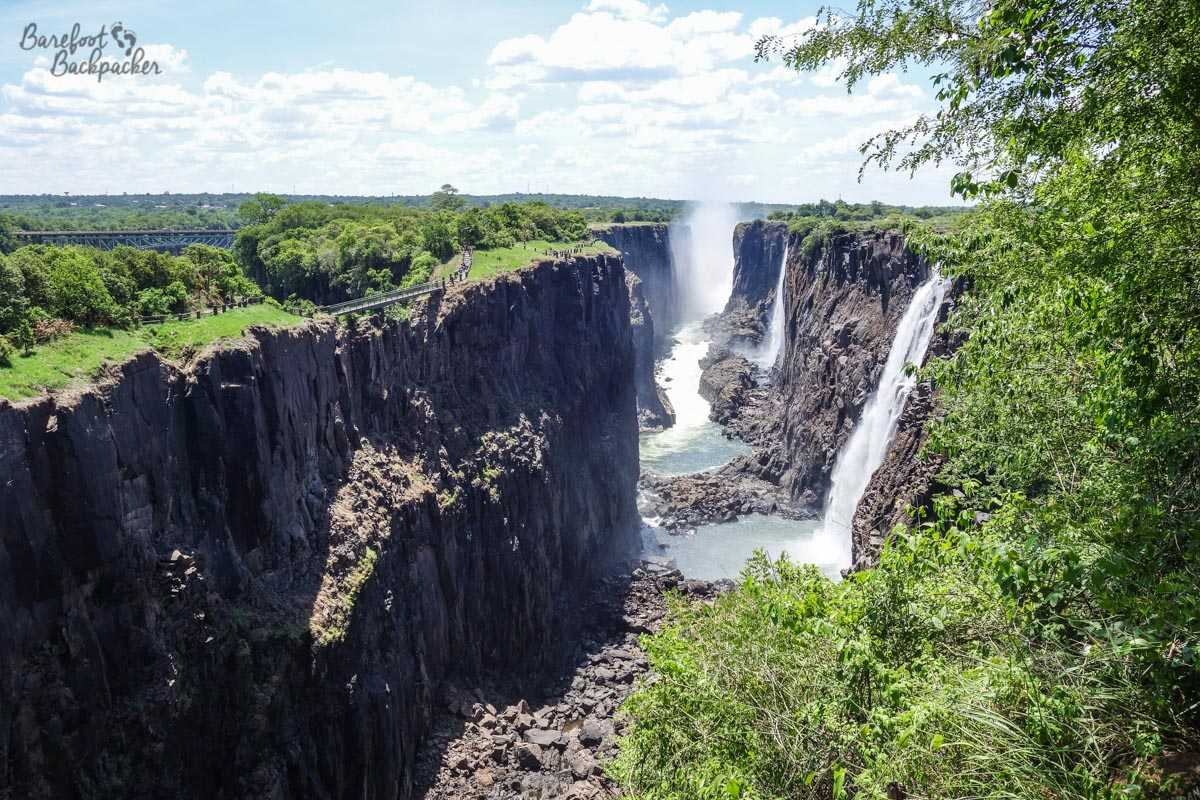 Looking across Victoria Falls – the water cascades into a small chasm either side of sheer rock cliffs. Lots of spray.