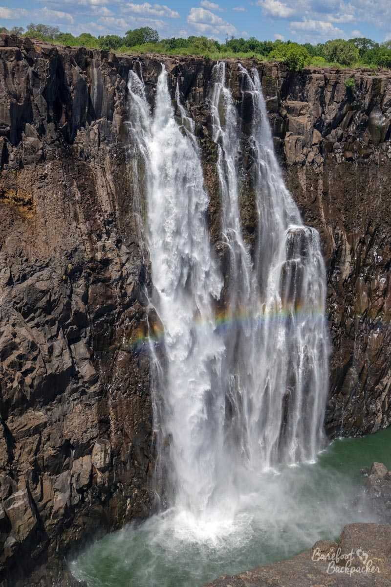 The Rainbow Falls at Victoria Falls; there's a rainbow effect often visible across the water as it falls