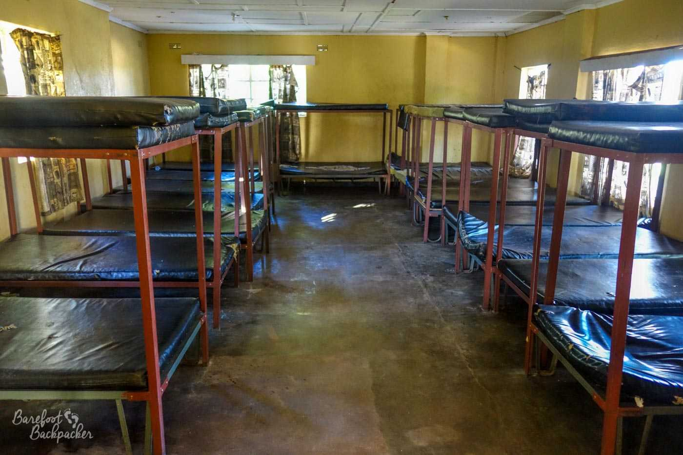 The empty, austere, minimalist, dorm room – the cheapest accommodation available. There's 28 beds in shot, in very close-fitting metal two-bunk beds, and there's a smaller room behind the camera with four more bunks.