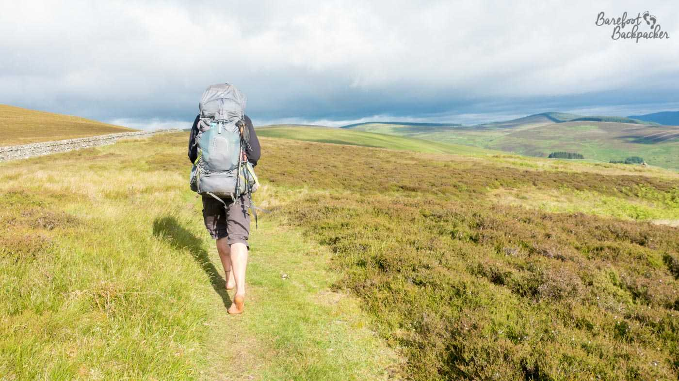 The Pentland Hills, in the lowlands of Scotland. A man hikes along a grassy footpath, barefoot, with a large backpack, under a bright but grey sky. He is surrounded by nothing much more than green rolling hills and a sense of calmness with the world.