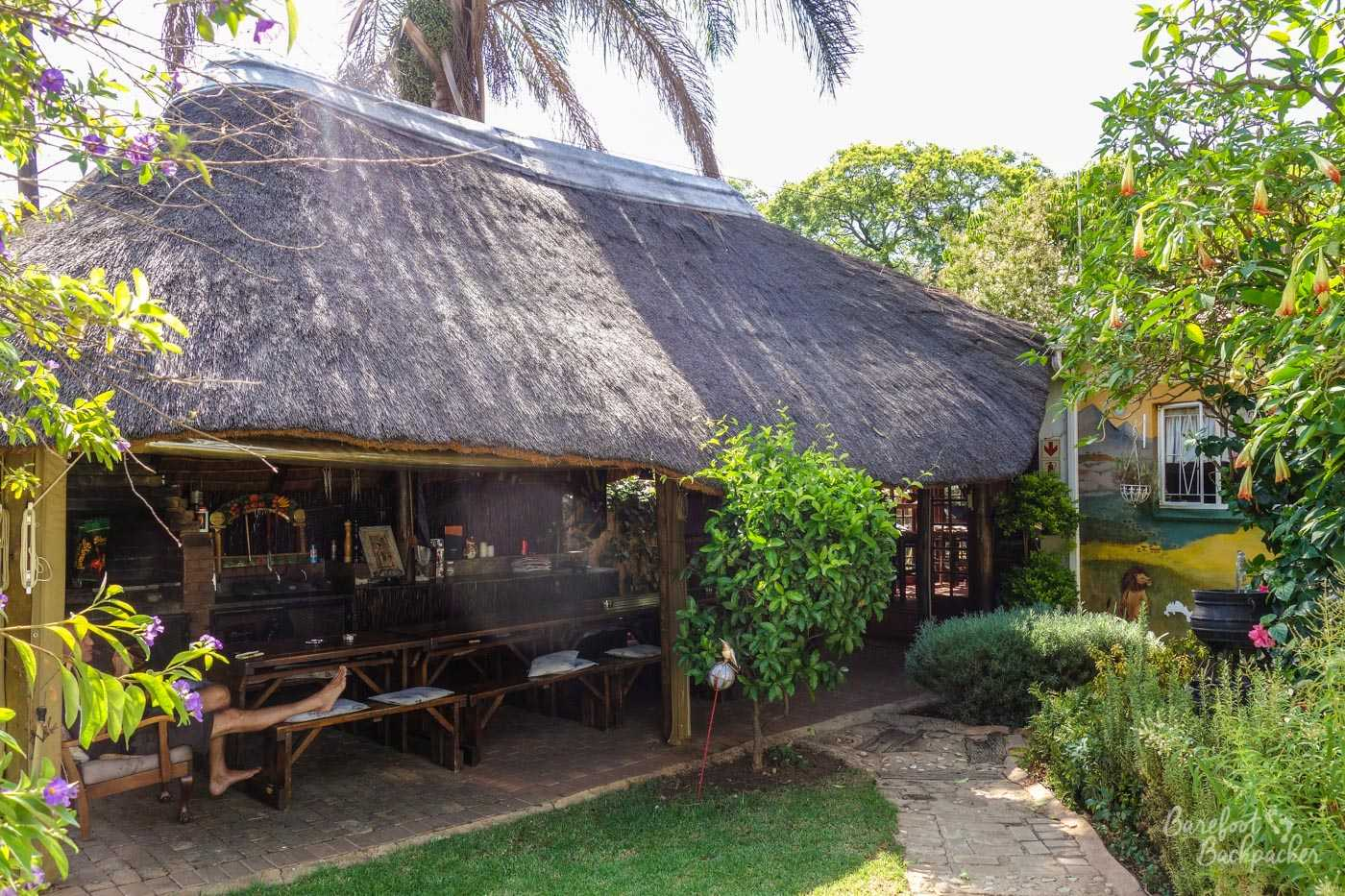 Thatched open-sided hut used as the outdoor dining area and braai in the Pretoria hostel.