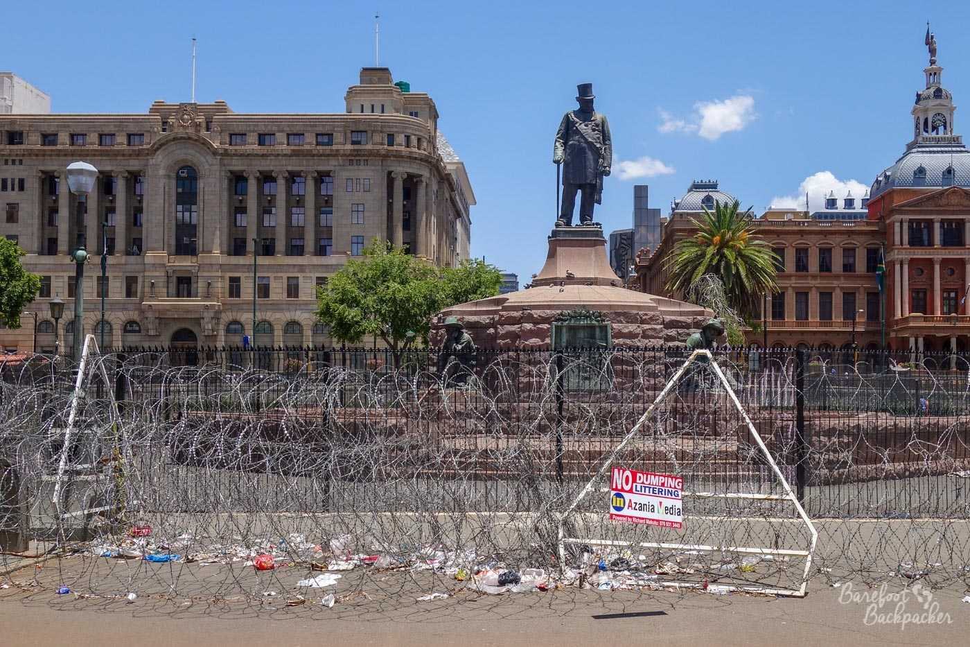 The Paul Kruger statue in the centre of Pretoria, surrounded by barbed wire and lots of litter