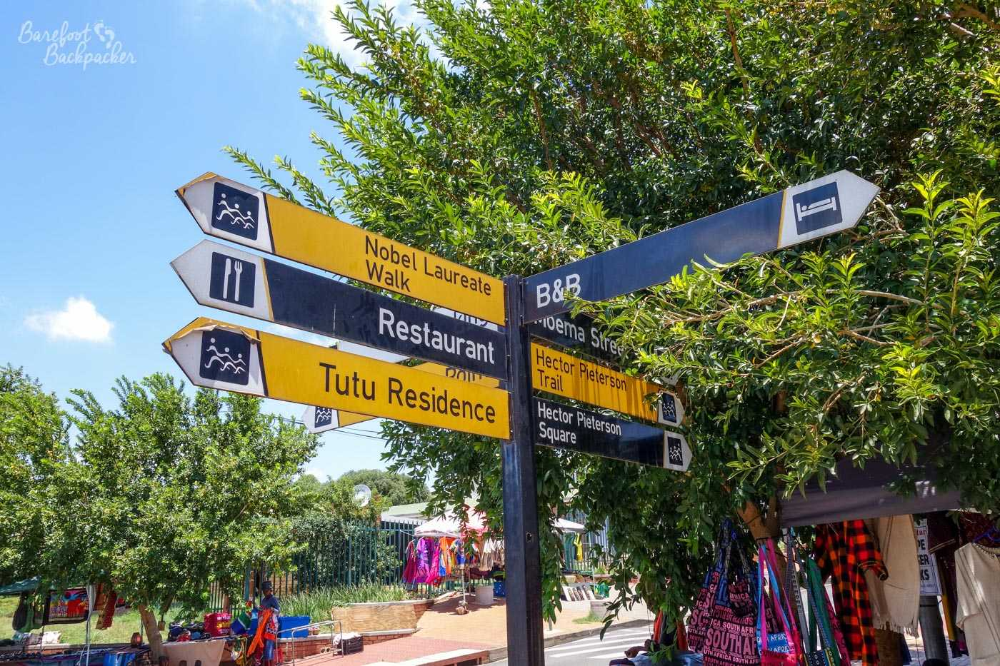 Signpost in central Soweto showing directions to Tutu's House and Hector Pieterson Memorial, amongst other things