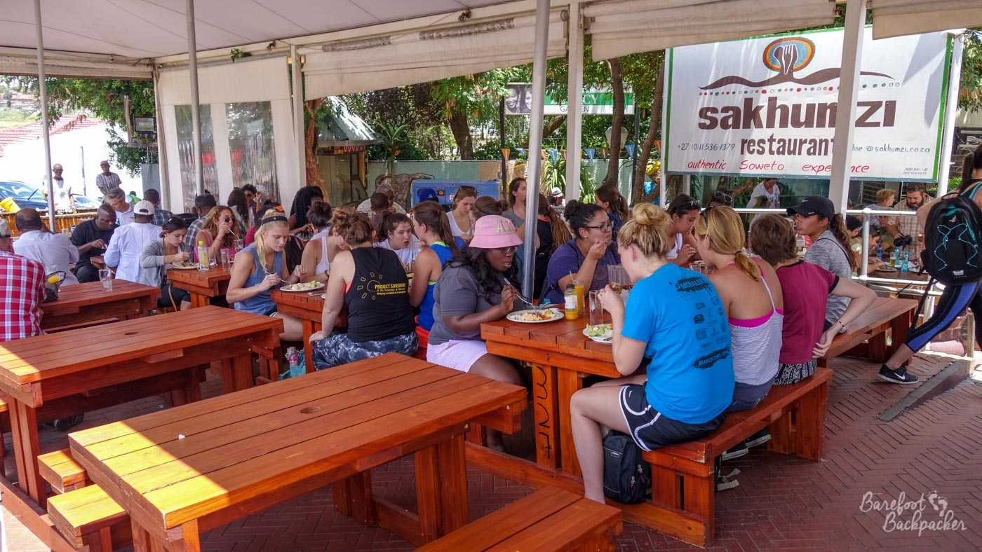 A group of mainly white tourists sitting having a meal in an outdoor café in the centre of the South African majority Black township of Soweto.