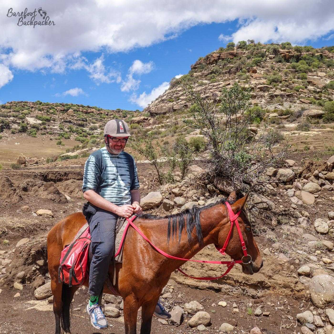 The Barefoot Backpacker, not barefoot, doesn't look entirely comfortable on top of a pony in the Lesotho rocky scenery. He is not a cowboy.