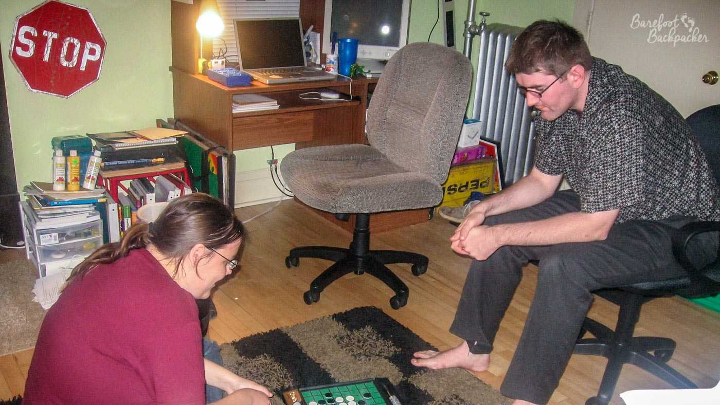 Two people in a student's front room, playing reversi / othello. One of them (me), a man, is sat on a chair on the right of shot. The other, a woman, is sat on the floor to the left of shot. The room is a mess. Obviously.