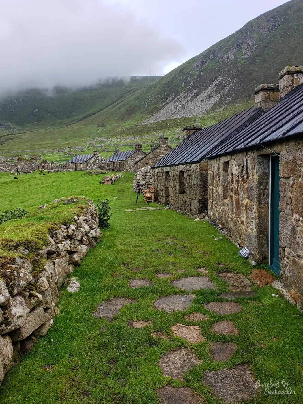 A look down the main road at the settlement on Hirta, with fields on the left and the ruins of stone cottages on the right.