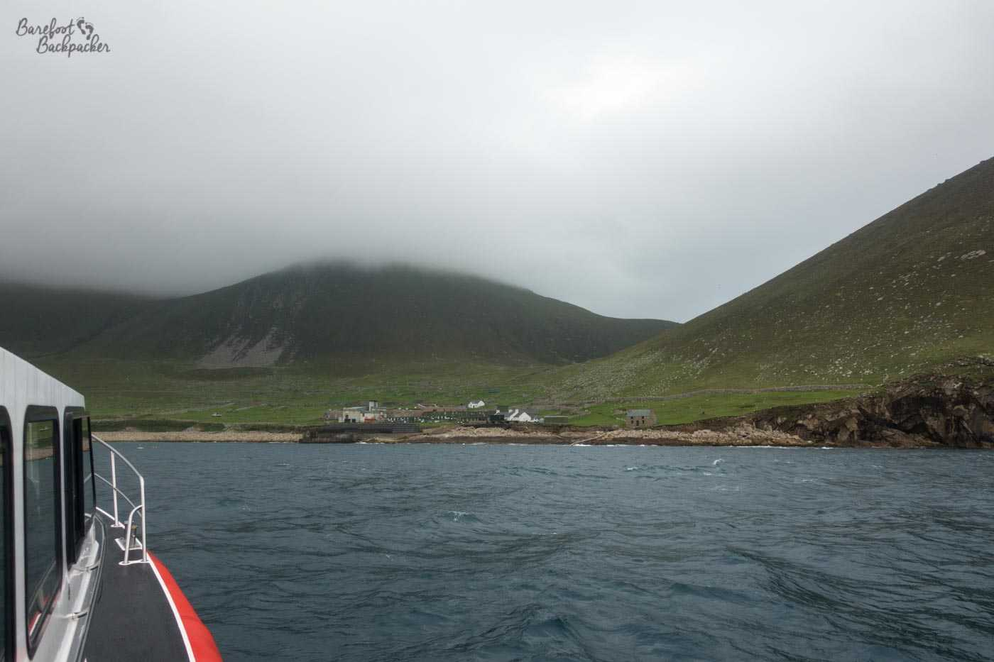 The first view of the harbour on Hirta, as seen from the boat. The small collection of houses look very exposed, with open country around and large hills looming in the background, topped with cloud/mist.