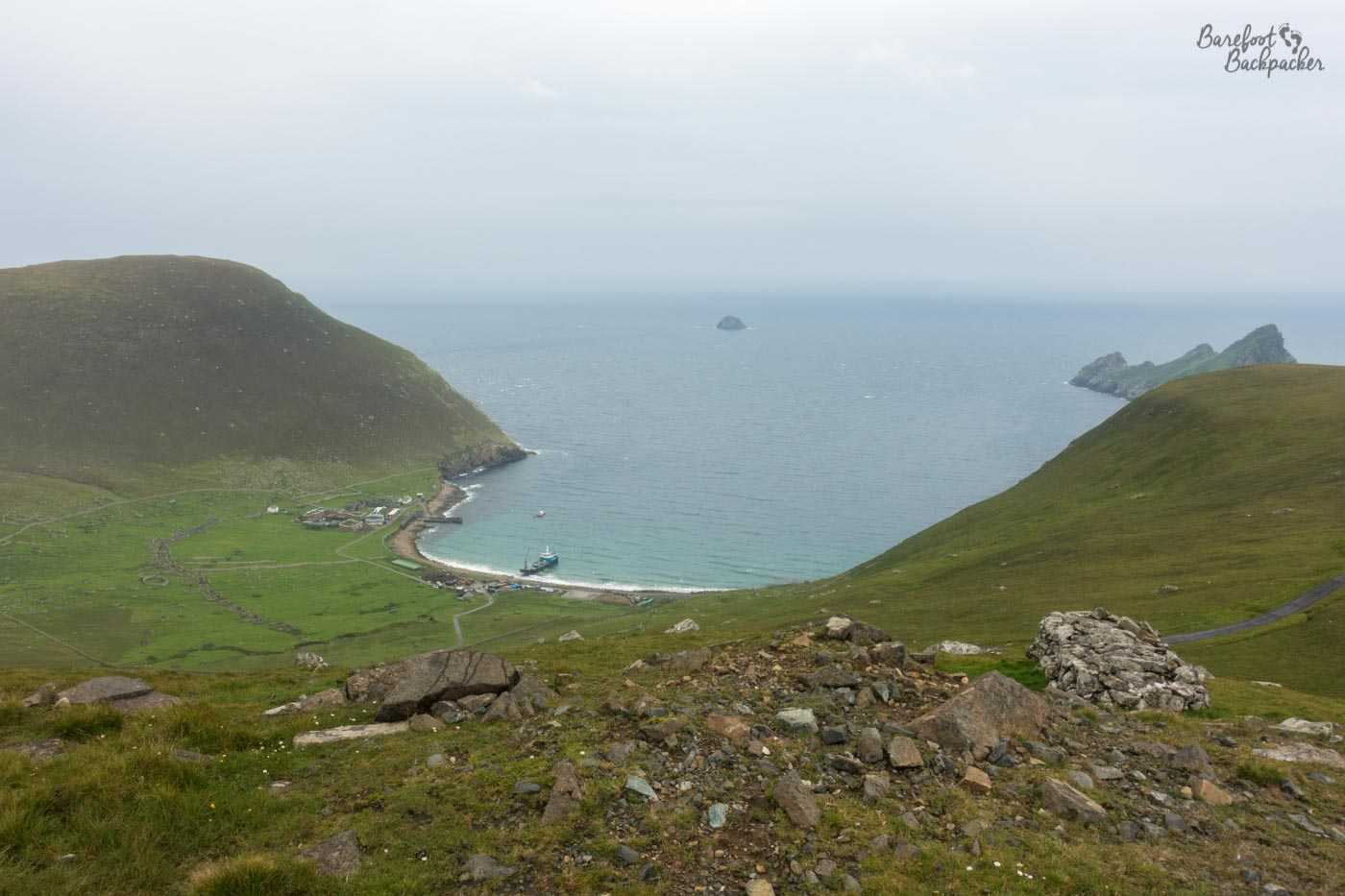 Another view of the harbour on Hirta, as seen from another of the hills that overlook the settlement. The bay is curved, and the lone ship rests in the middle of the calmed natural harbour.