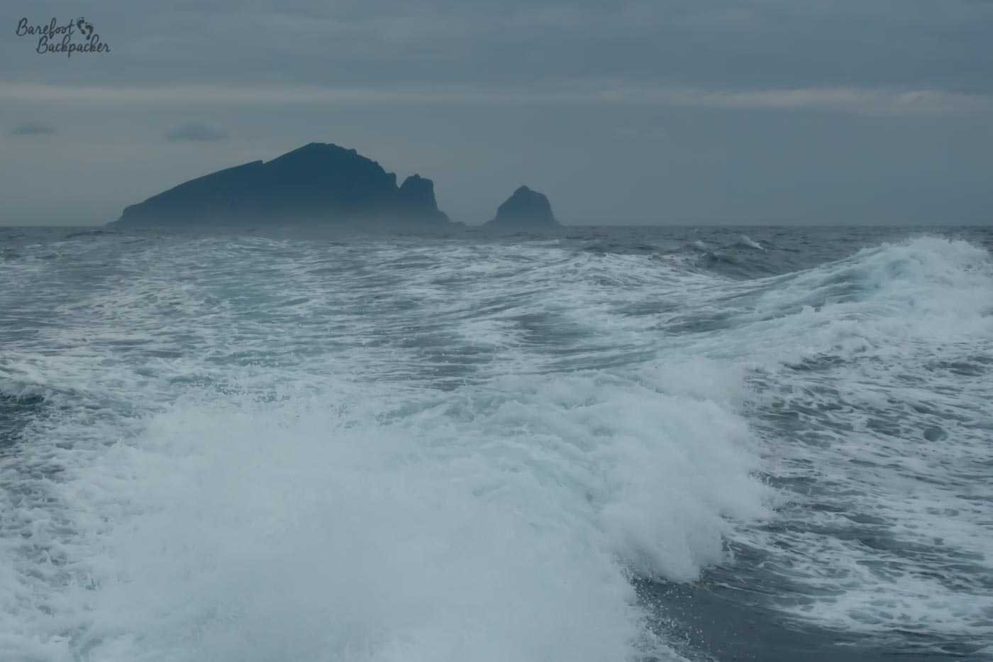 View of the rock stacks around St Kilda from the boat. There's a fair amount of spray in the sea and the sky is quite grey – it was a very windy and wet day.