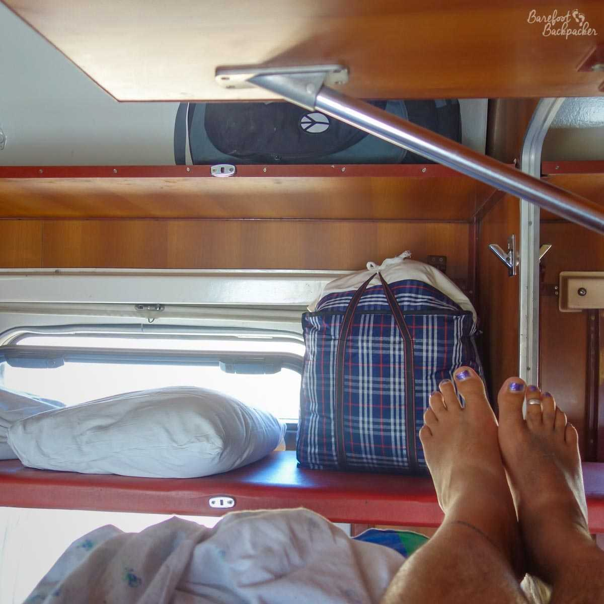Inside a train in the former Soviet Union; showing the luggage rack and the lack of space on the bunk. Warning, contains bare feet.