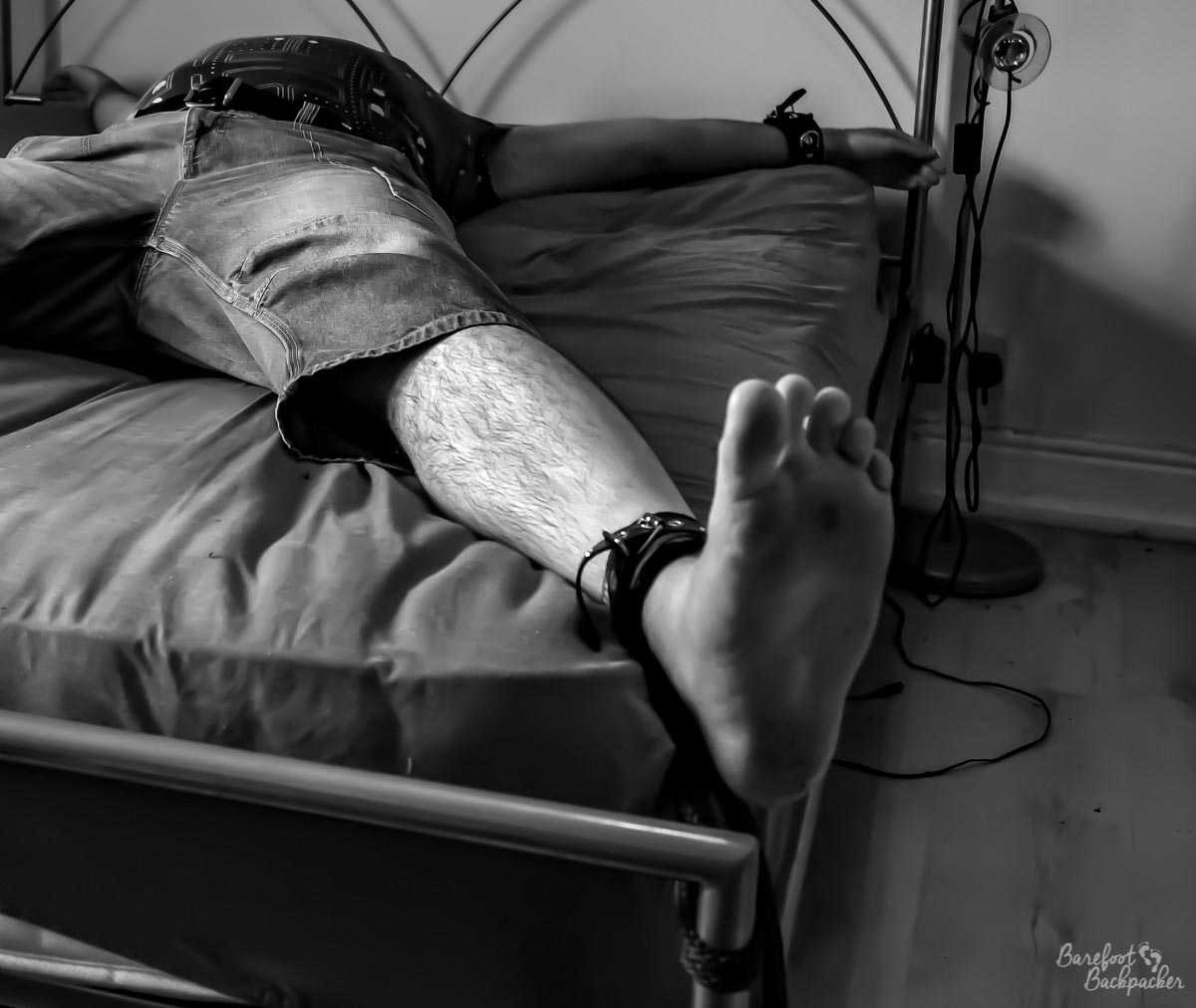 Man tied spread-eagled to a king-sized bed. He's wearing a t-shirt and long denim shorts, and is barefoot – his left foot is centred and focused. The image is in black&white.