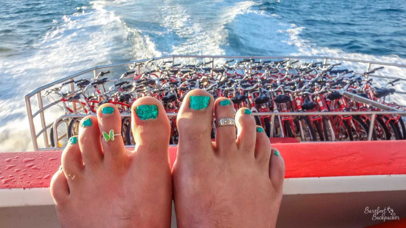 On board the ferry, as it sails across the sea. Two bare feet, green nail varnish, green butterfly toe-ring on middle toe of left foot, rest on the barrier that overlooks the lower deck of the ship, which is full to the brim of gleaming chrome bicycles.