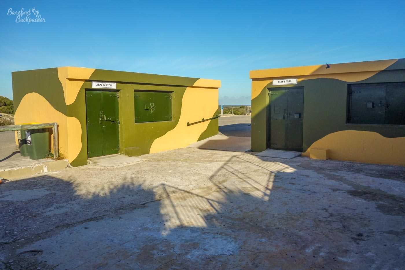 A couple of the buildings used for storage, maintenance, waiting around, etc, at Oliver's Battery. They're kind of camouflaged in yellow/grey decoration, which looks ... kinda odd atop a barren hill.