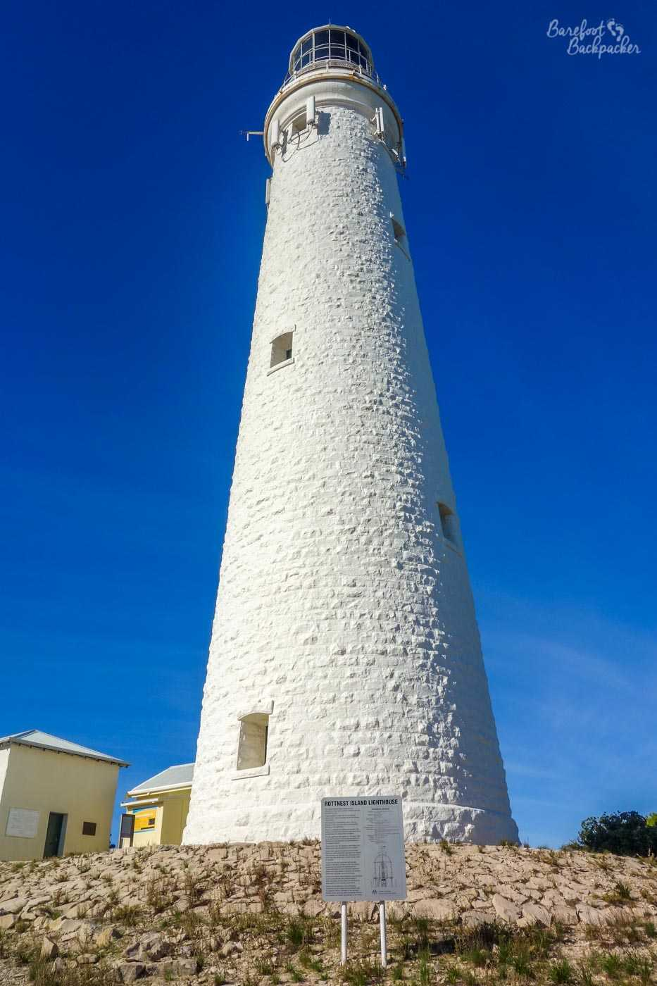 Close-up view of Wadjemup lighthouse; a large white cylinder standing bright against a clear dark blue sky.