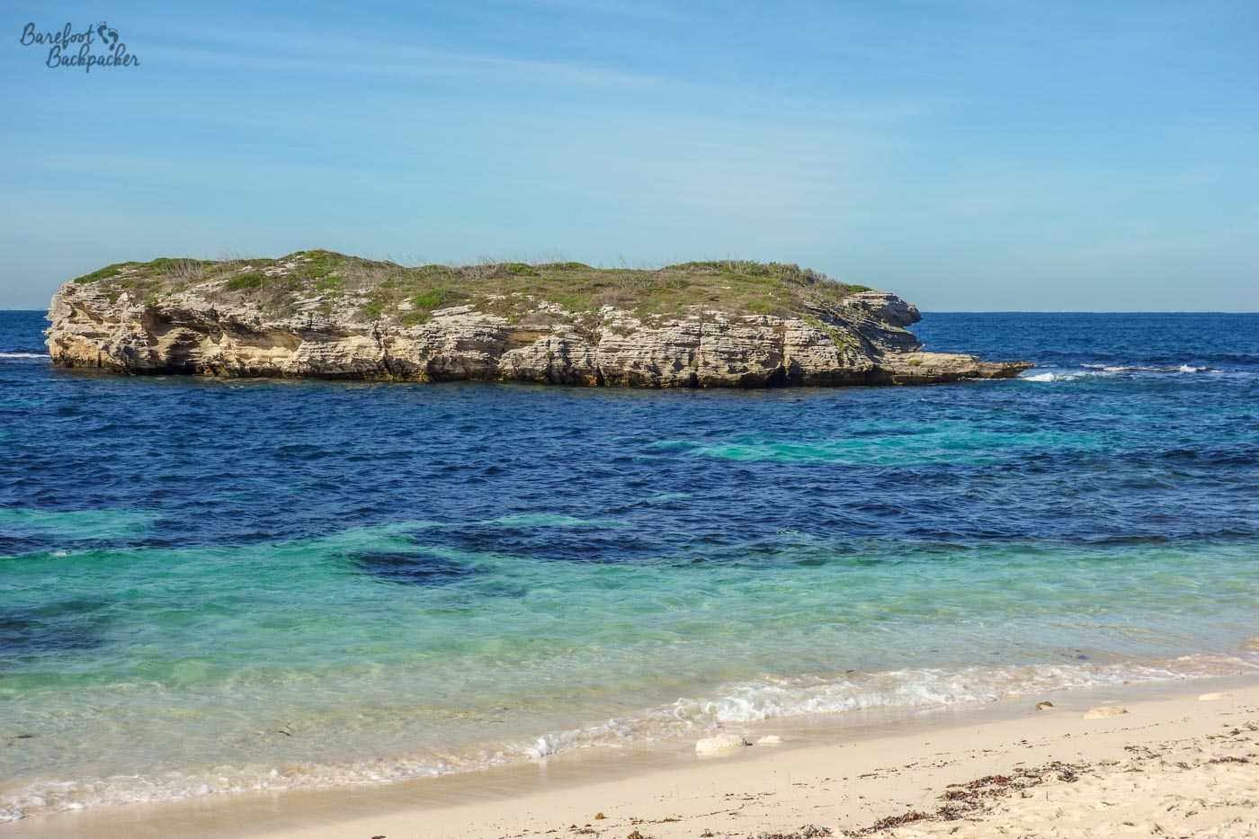 One of the beaches on the shoreline of Rottnest Island. The water is tropically clear blue, the sand pale, and a short way into the sea is a rocky island with steep cliffs. It's akin to the tropical paradise beaches you might have read about.
