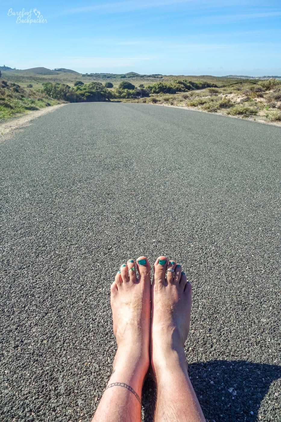 An empty tarmac road on Rottnest Island, no people or bicyclists about. The road disappears into the distance over a slight hill. There's grassland to either side. In the centre of the shot, in the middle of the road, lie two bare feet, pointing upward, just resting with their heels on the tarmac.