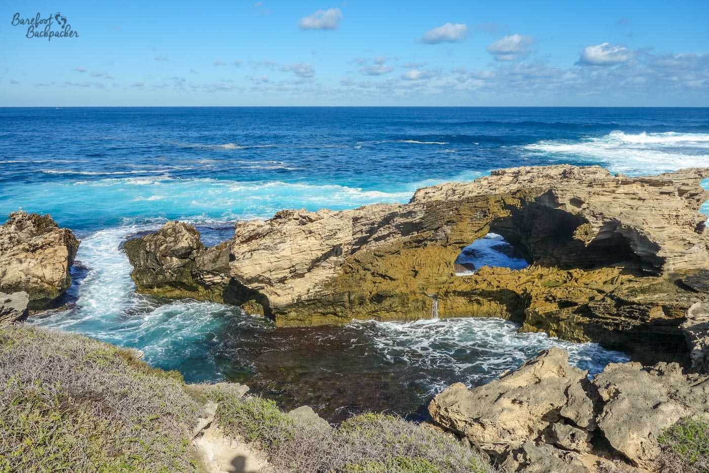 One of the many series of rock features near to West End. Much of this part of the coast of Rottnest Island has similar features – gnarled, light brown, jagged pieces of land mostly worn away in irregular ways by the actions of the sea, leading to natural caves, rock bridges, etc.