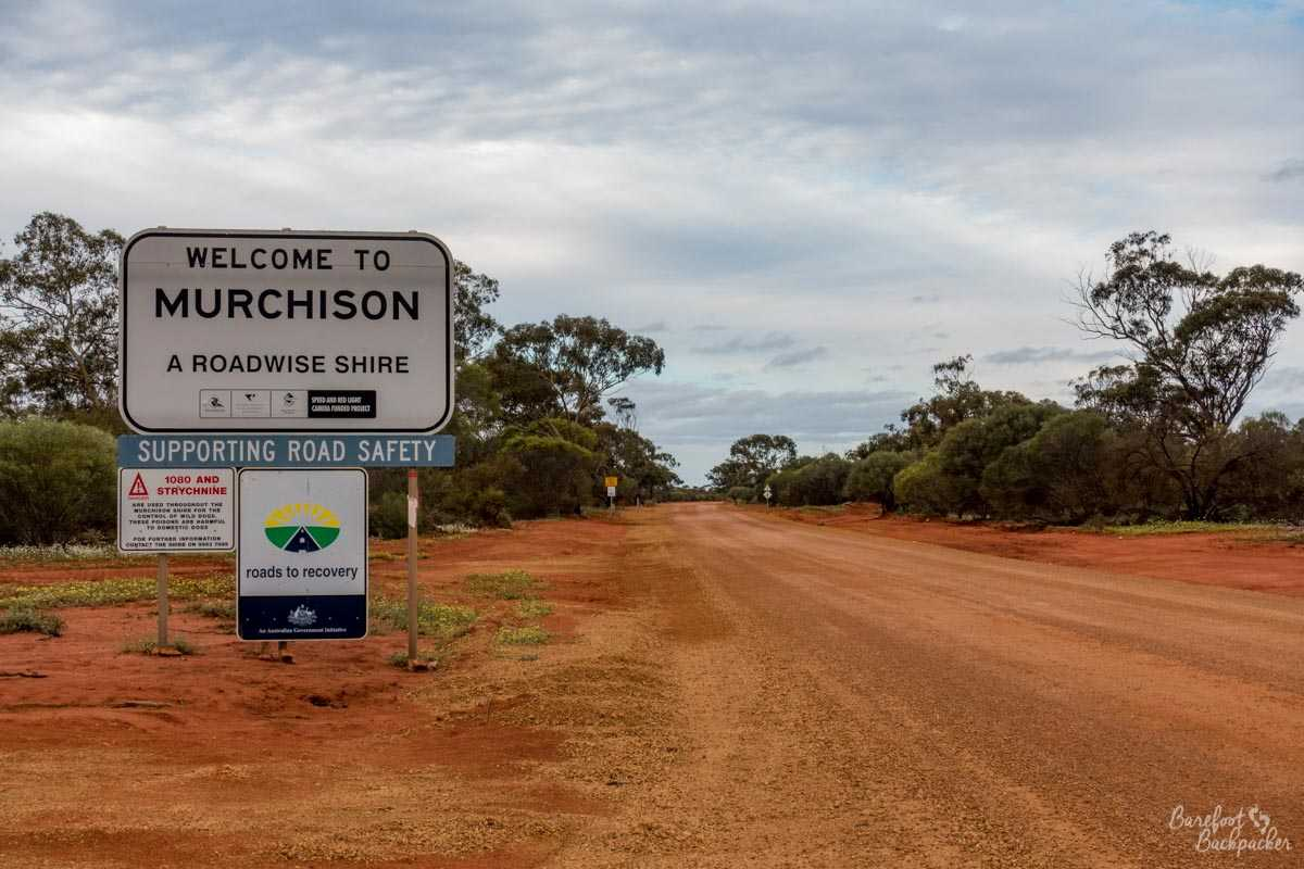 Signpost welcoming you to the Shire of Murchison. It stands next to a dusty orange stony road. This is not an urban metropolis.