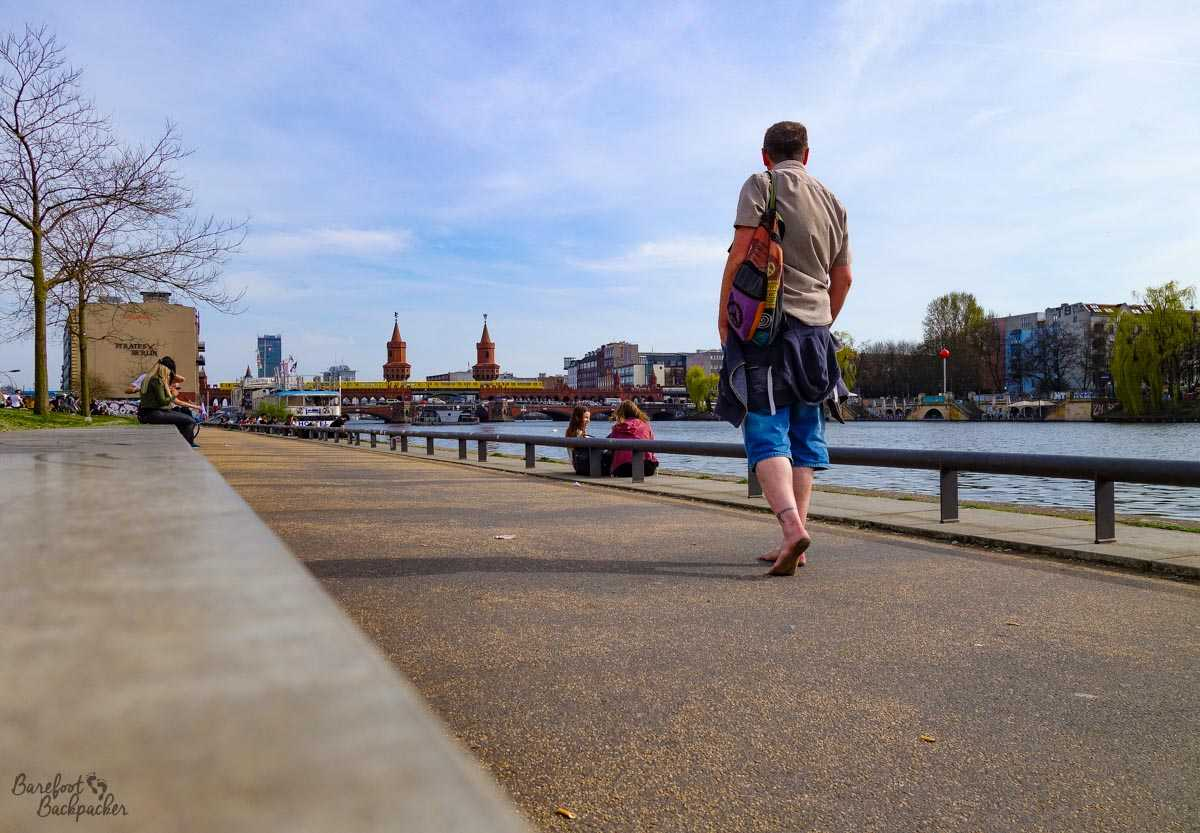 Barefoot man with small backpack walking along the waterfront in Berlin.